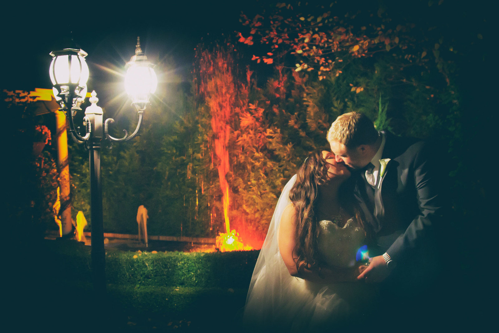 Bride and groom kiss at night among the light of a lantern.