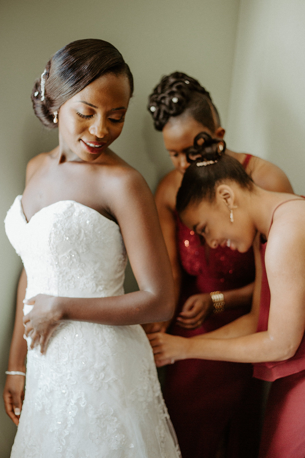 Bridesmaids helping the bride get her wedding dress on during his Minneapolis wedding