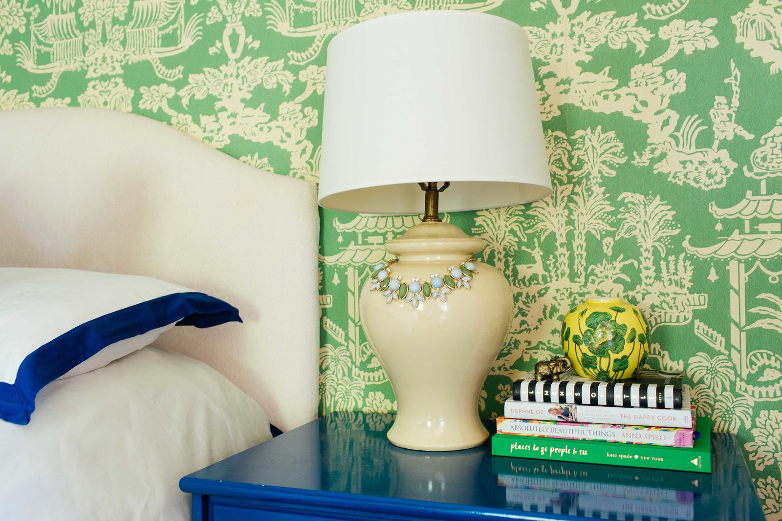A white bed and blue end table  in front of a green wall papered wall.