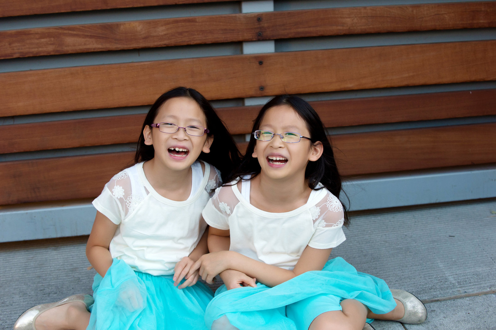 twin girls wearing matching outfits share a laugh