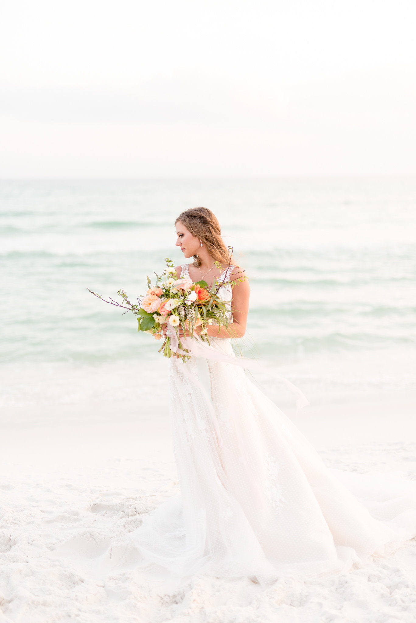 Bride stands on beach with bouquet.