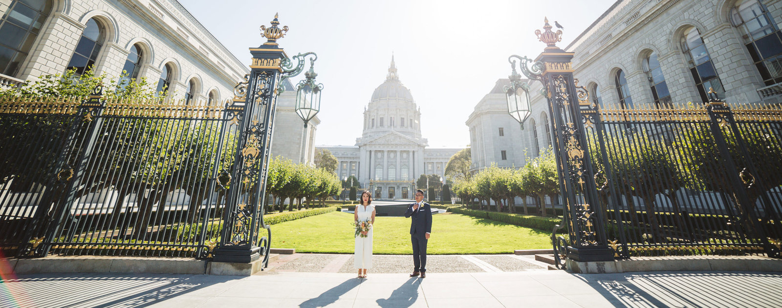 wide shot of couple standing behind city hall in Van ness park