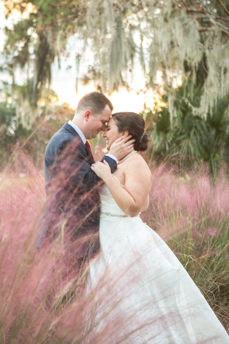 bride and groom touching foreheads in pink fluffy muhly grass