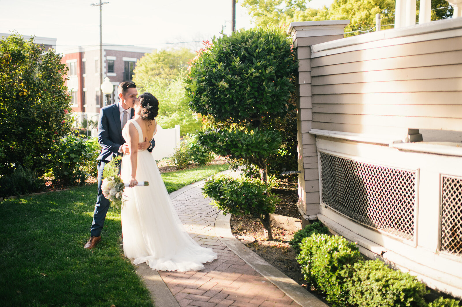 Newlyweds share a celebratory kiss near the Mansion after their ceremony as the golden hour light illuminates them.