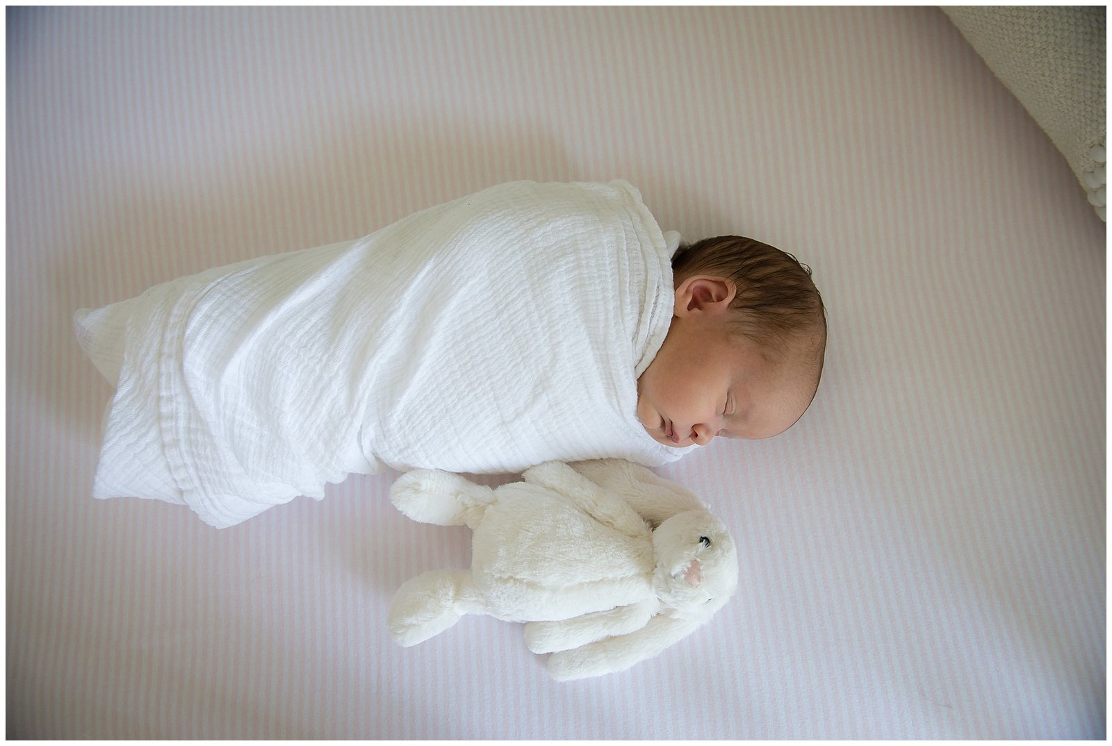 Newborn baby girl swaddled in crib with stuffed bunny Emily Ann Photography Seattle Photographer