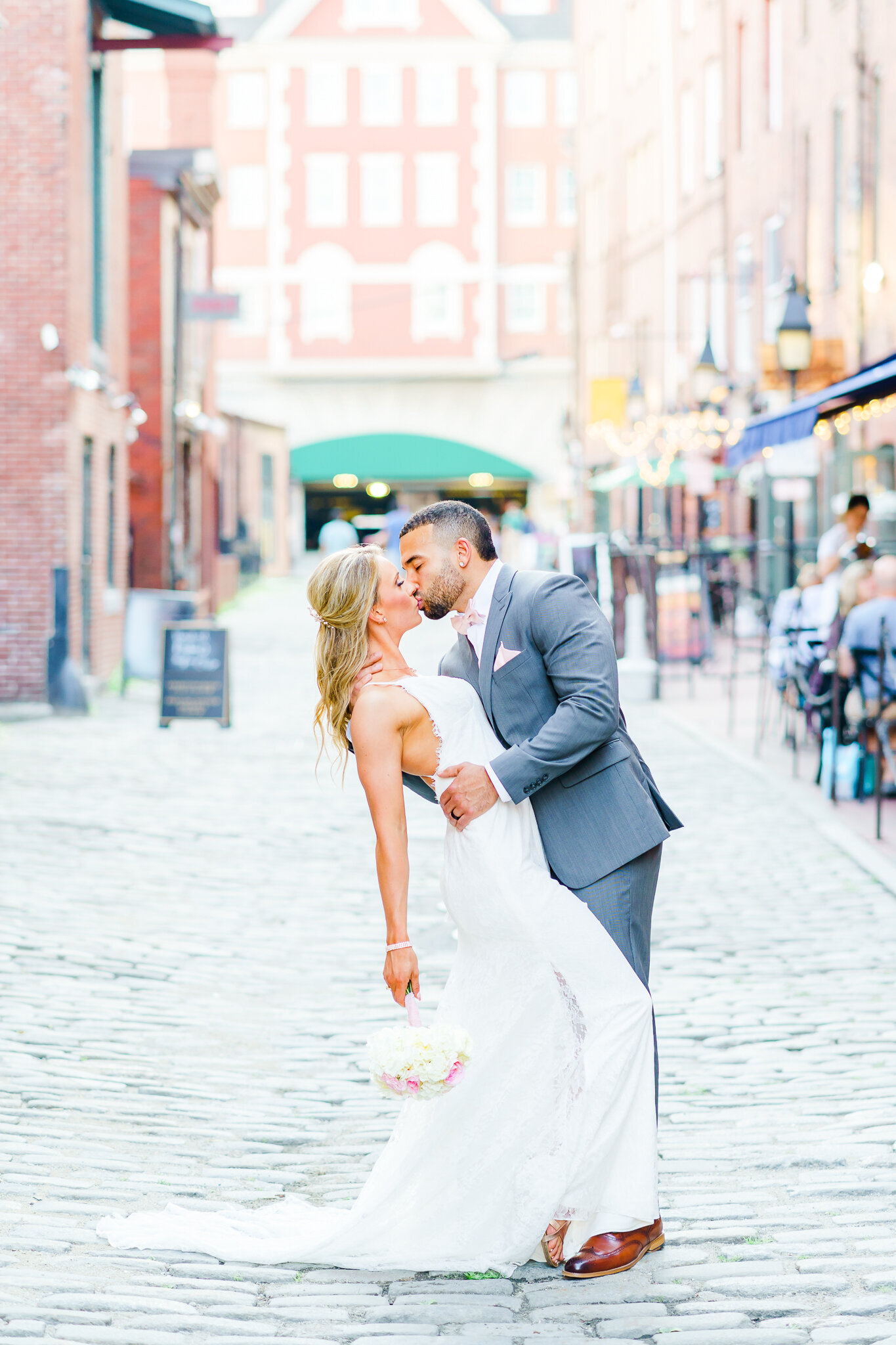 Wedding couple kissing in busy New Hampshire street