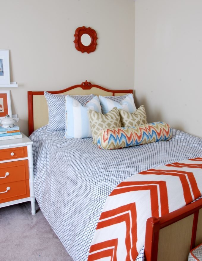 A dark orange and beige bed with a mirror above.