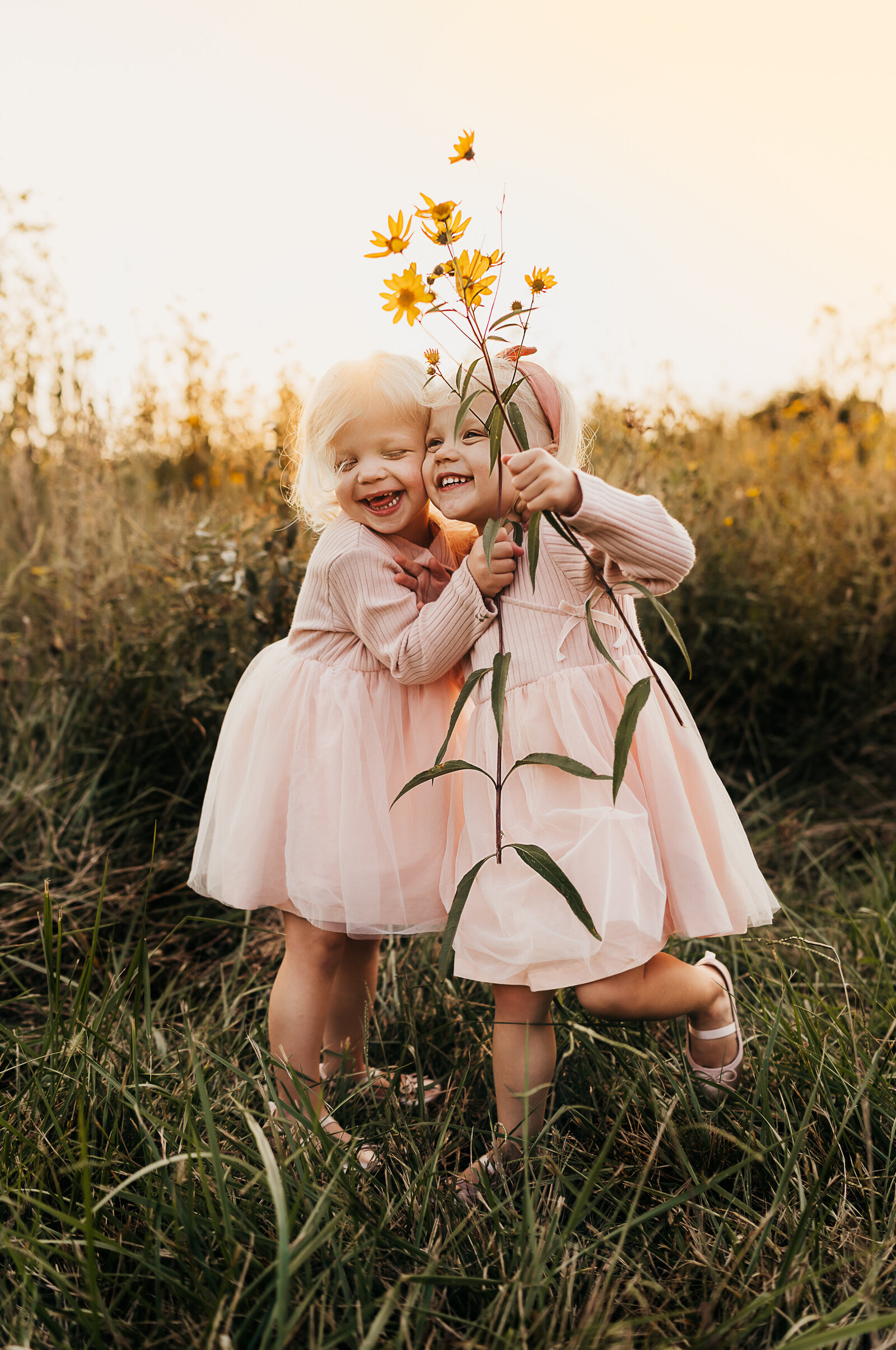two little girls holding flowers and laughing
