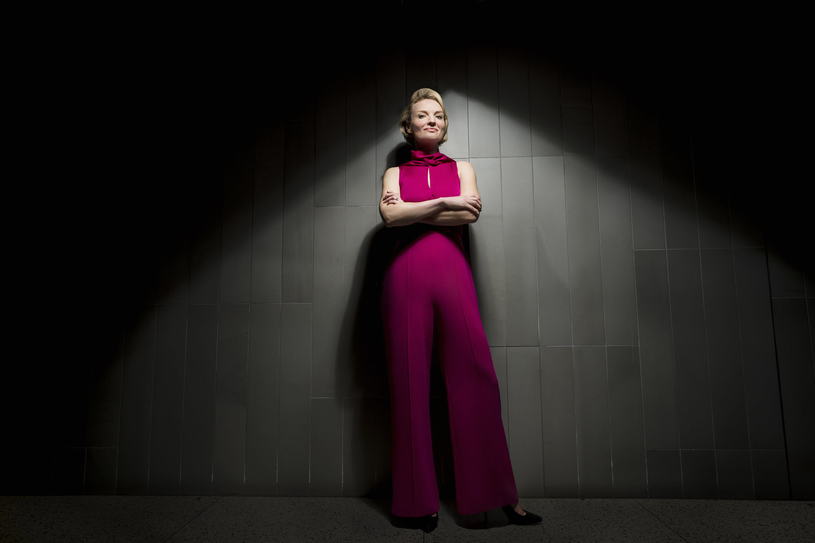 Female CEO stands in a strong pose with her arms crossed wearing a fuscia jumpsuit under dramatic lighting