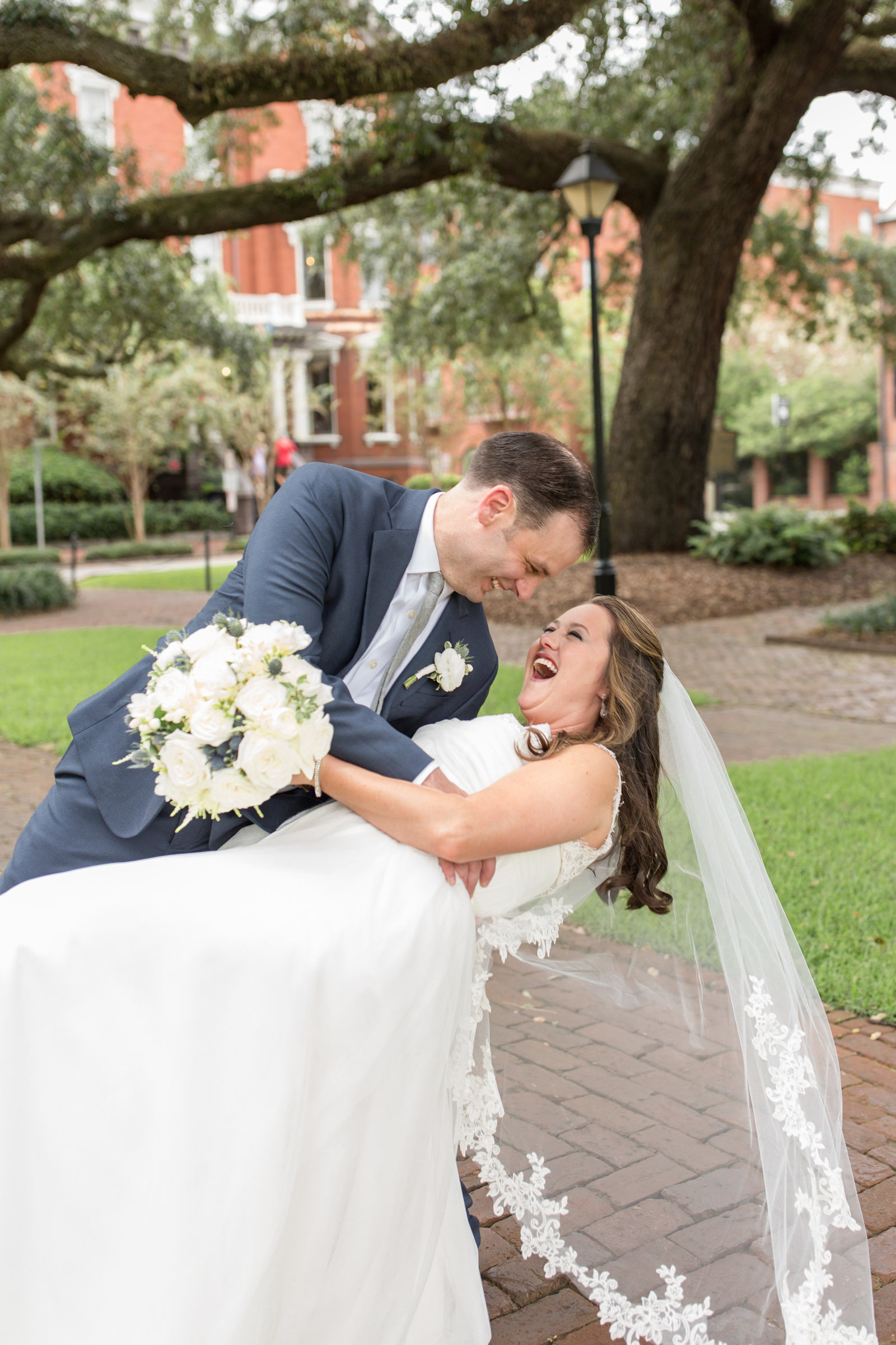groom dipping bride and she is laughing in front of kehoe house in savannah