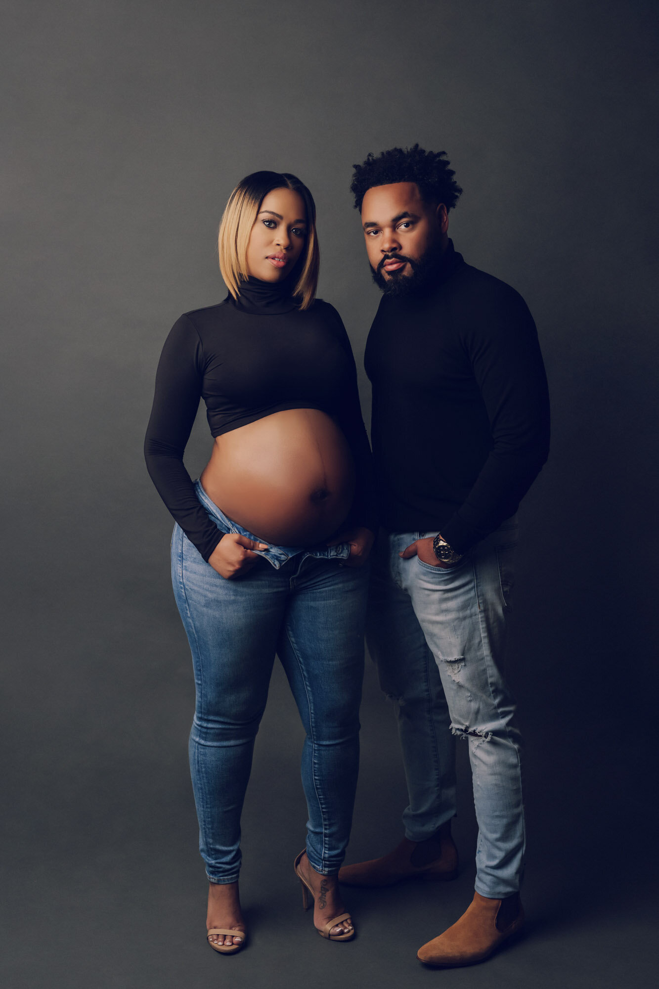 Maternity portrait of a man and woman in jeans and turtlenecks. Luxury portraits.