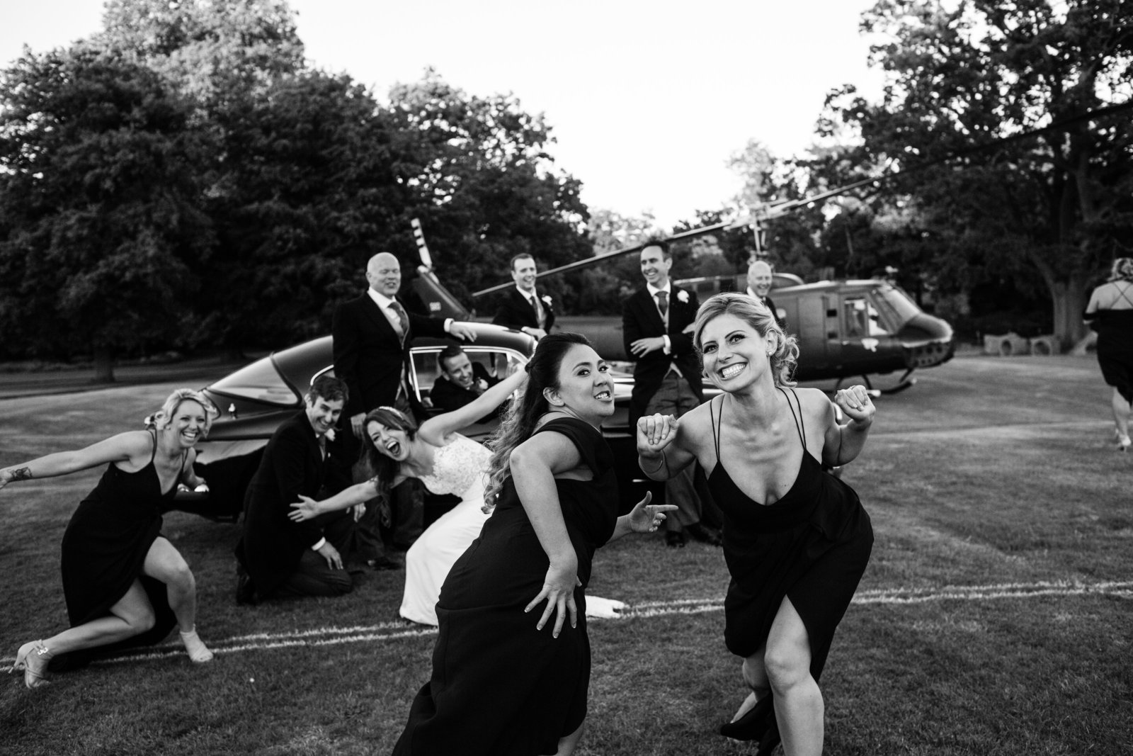 Formal wedding photograph is disrupted by merry Bridesmaids who laugh and pose funnily in front of Groomsmen in Suffolk.