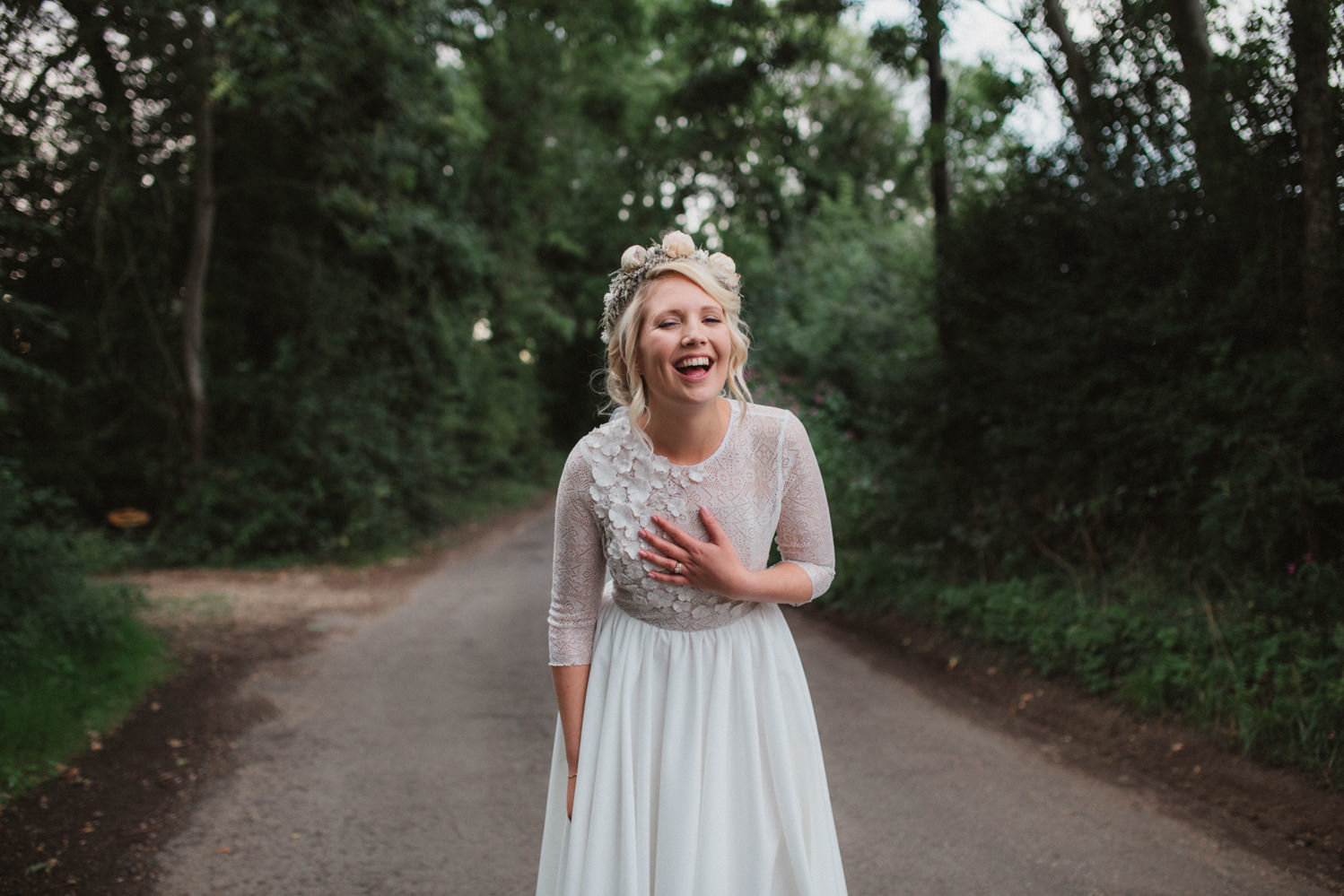 Bride laughing after her wedding down a country lane in Woodbridge, Suffolk