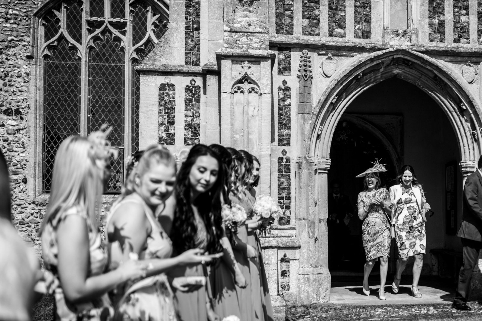 Two guest appear laughing in a church doorway in Norfolk. The crowd outside are lined up as they hold off throwing confetti.