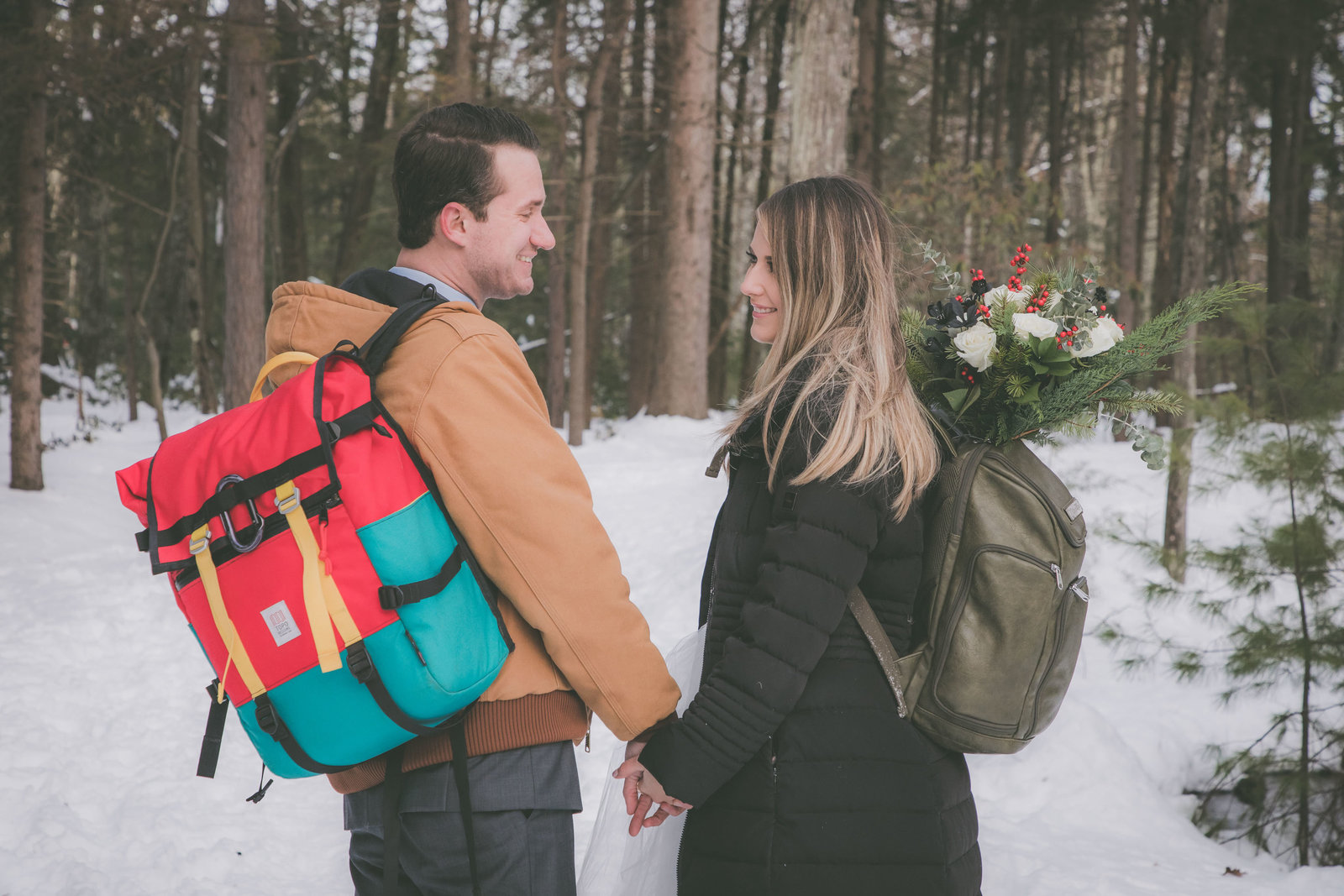 A couple looks at each other and smiles during their hiking elopement.