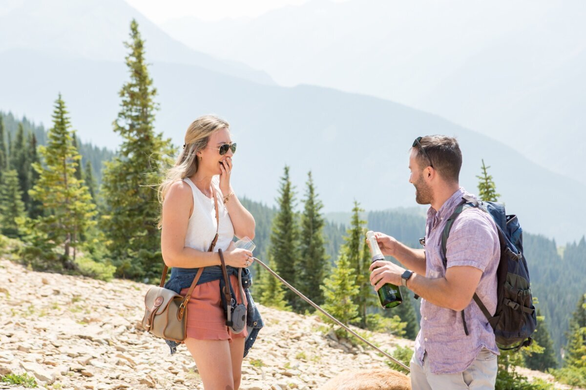 Popping champagne on top of Aspen mountain after proposing