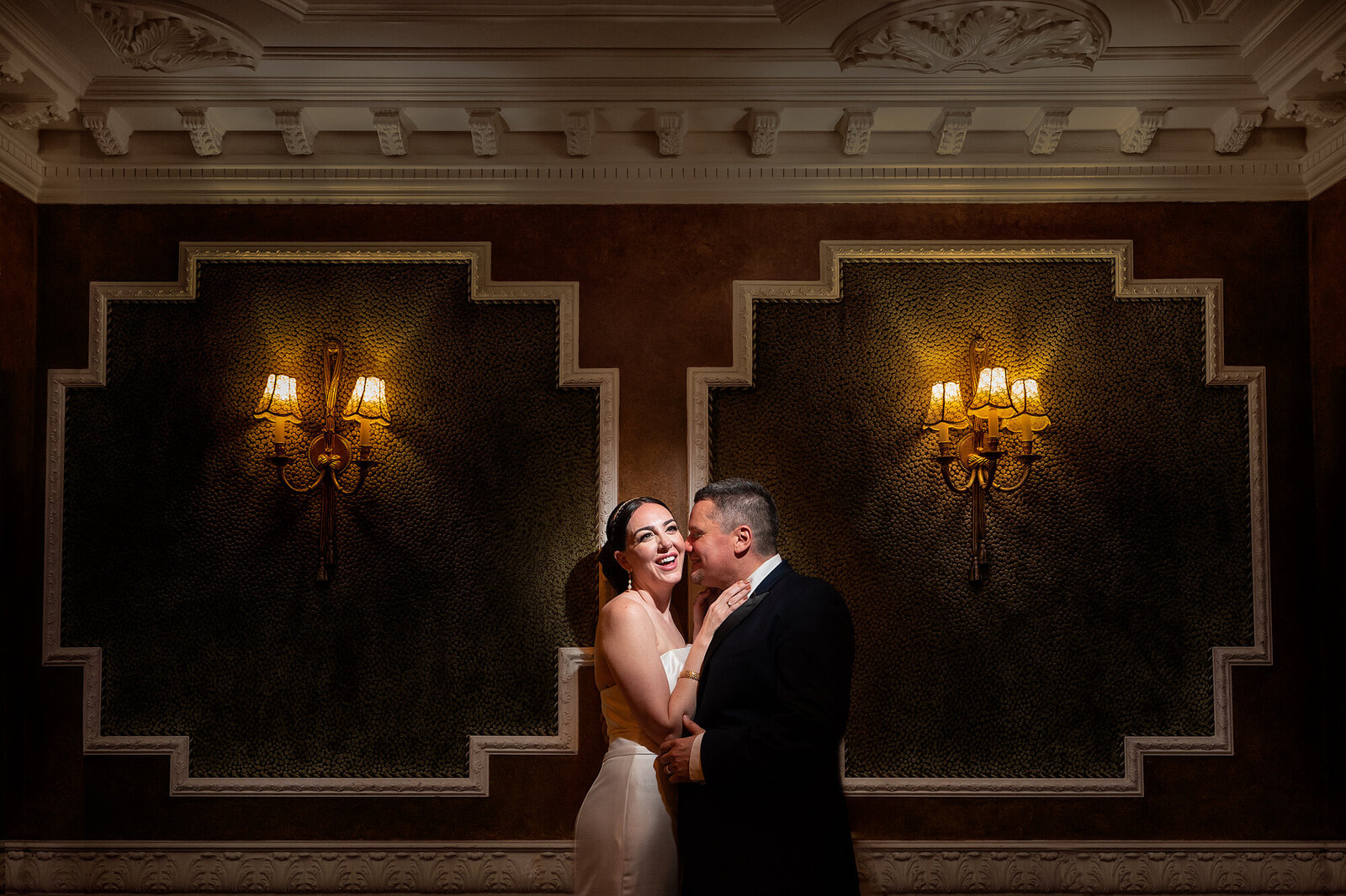 a beide and groom in front of a fabric textured wall and sconces at the Brownstone wedding venue