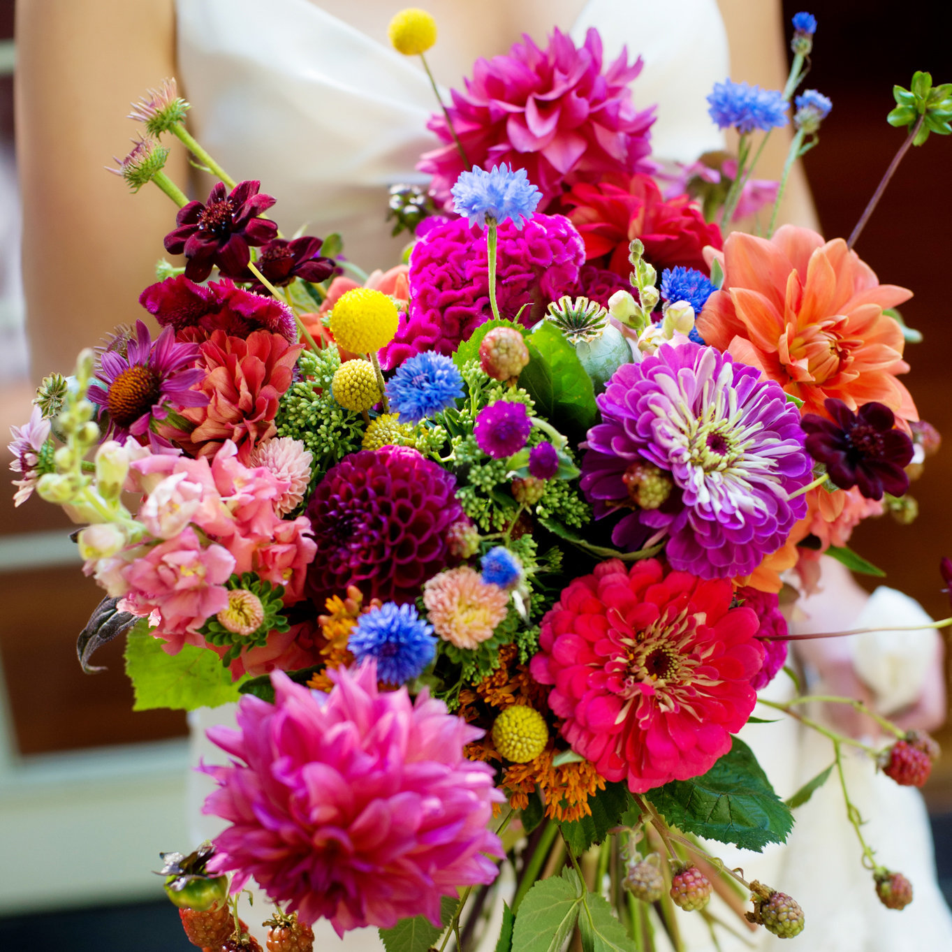 a close up of a bride holding a very colorful and bright wildflower bouquet