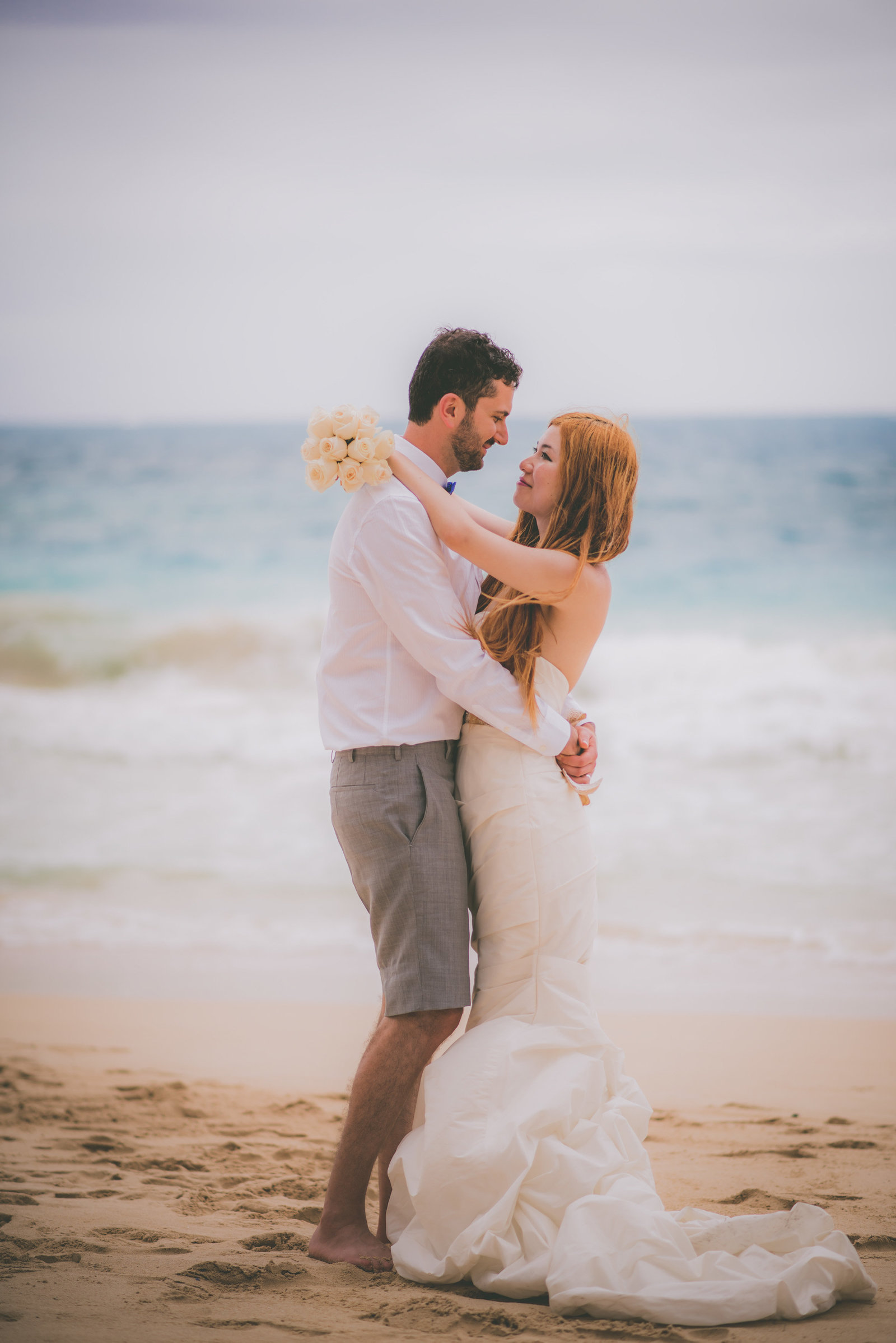Bride and groom stare at one another on Oahu beach.