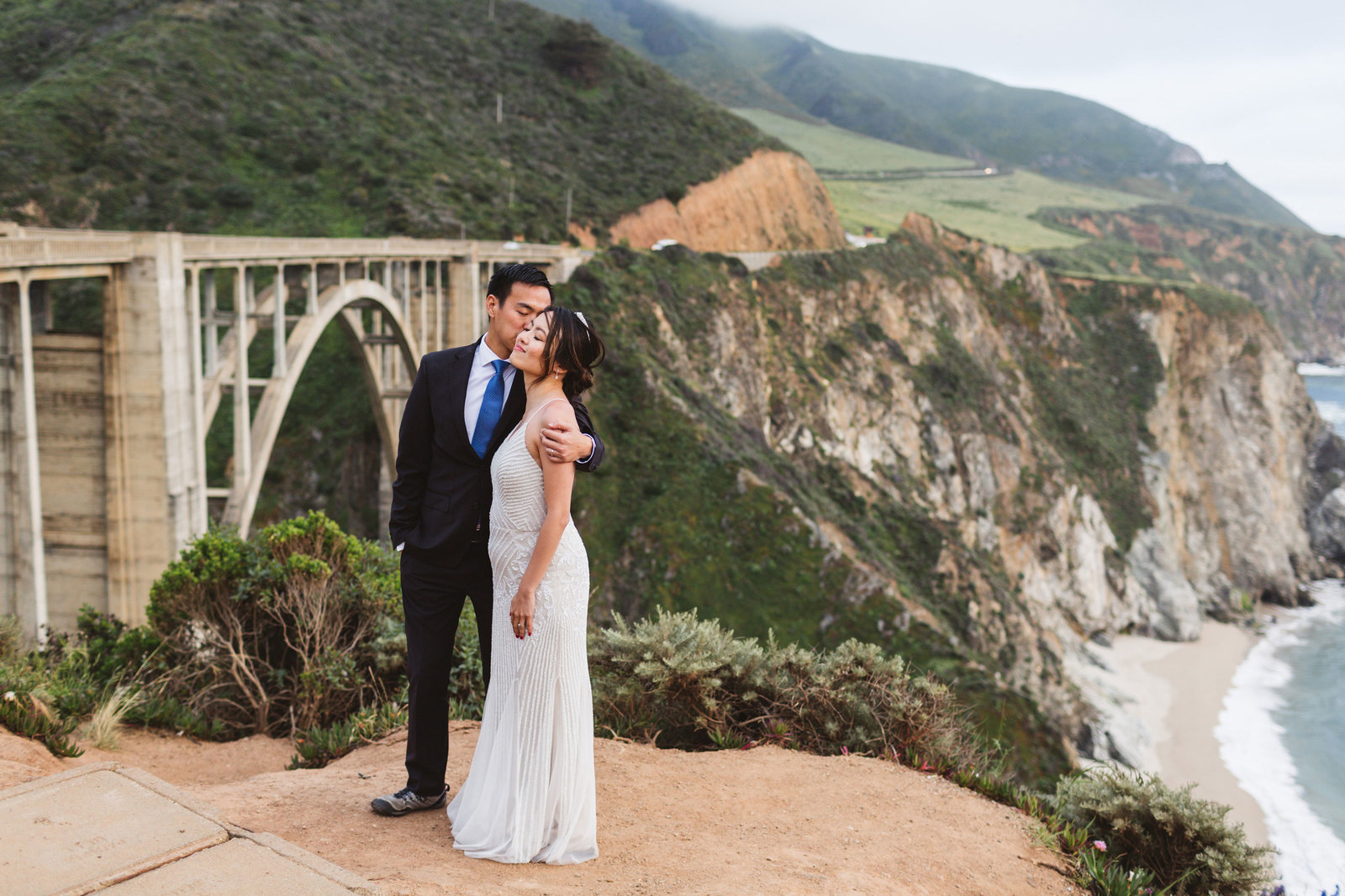 wedding couple kissing and snuggling with bixby bridge behind them