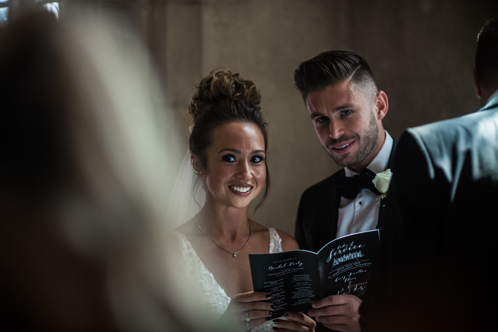 A couple look and smile at the camera whilst they sing hymns during their wedding ceremony at Hengrave Hall church.