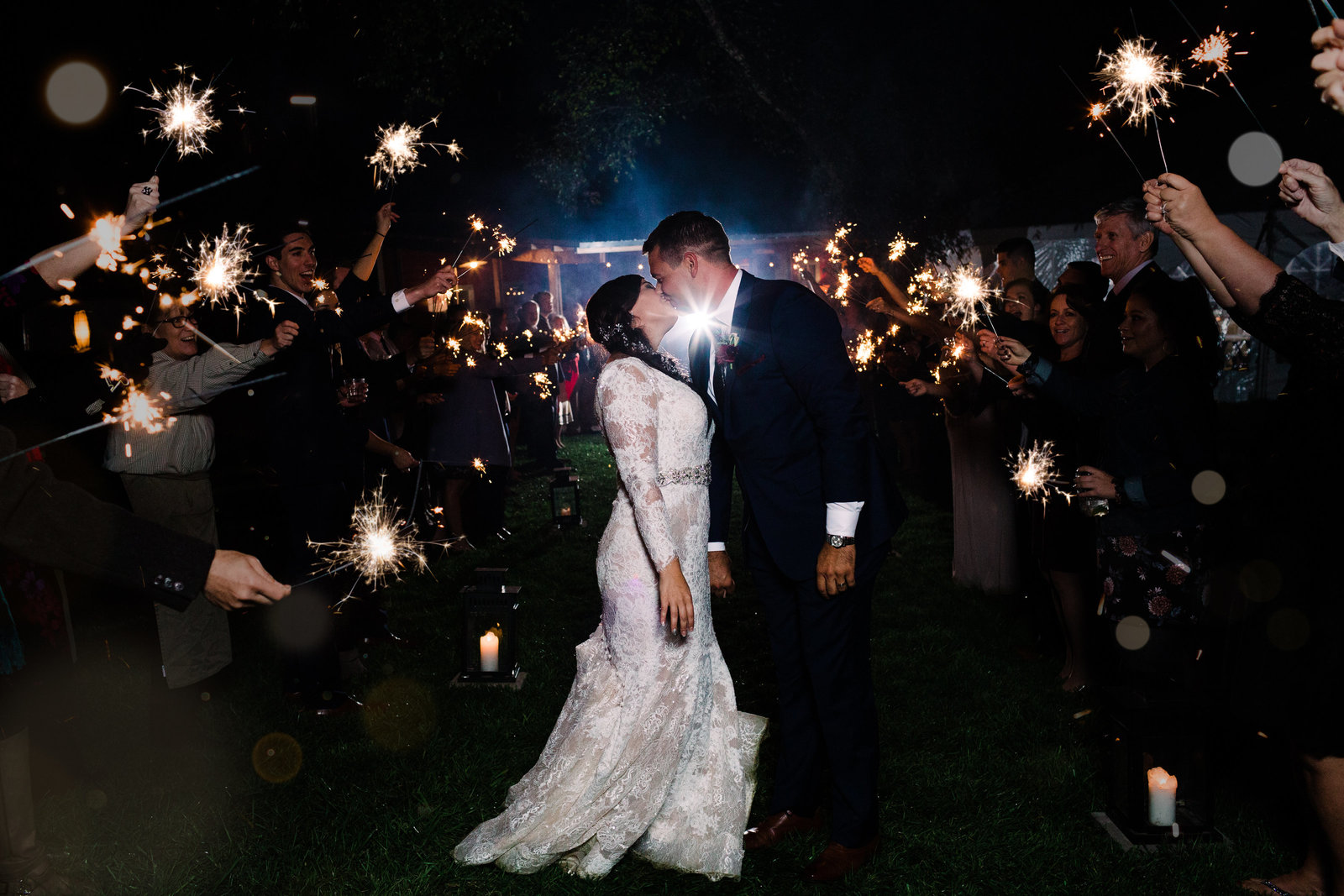 Bride and Groom, Corrie and Neal, stop for a kiss as their friends raise sparklers for their big wedding exit by Jackelynn Noel Photography