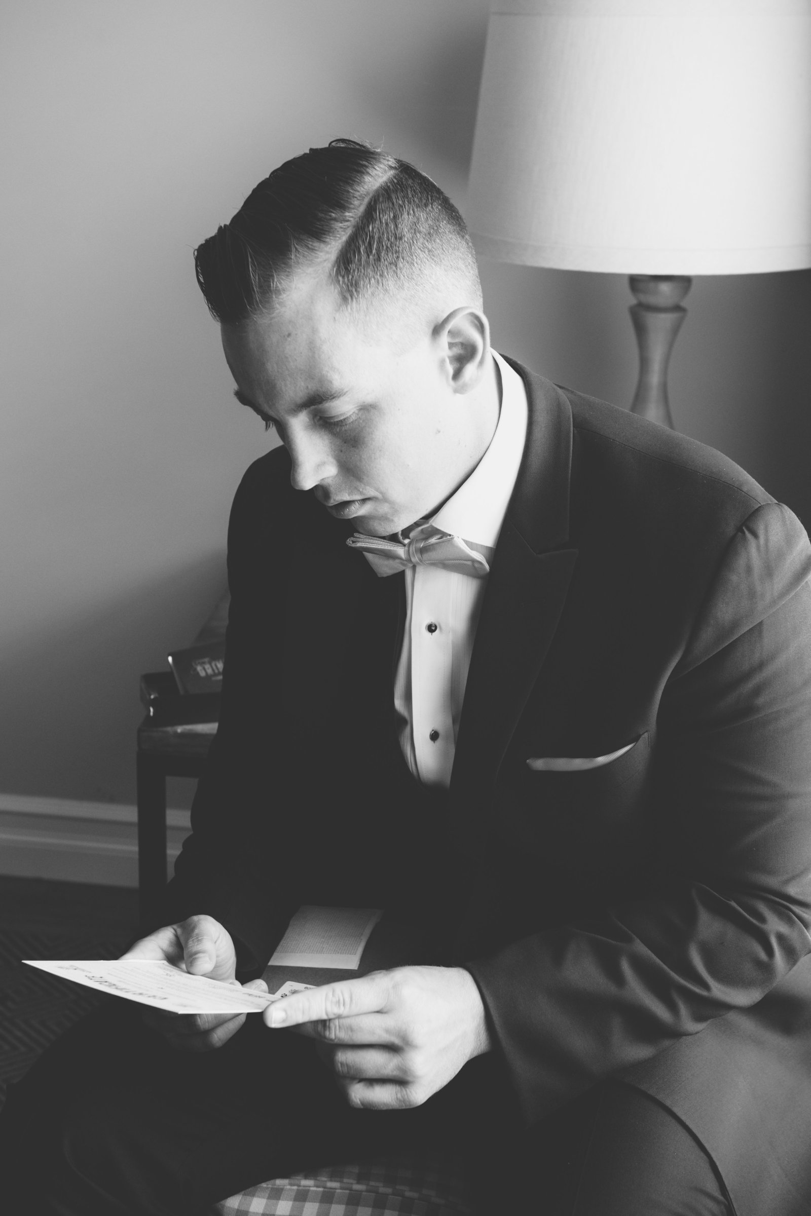 black and white photo of groom reading a note from wedding at Three Village Inn