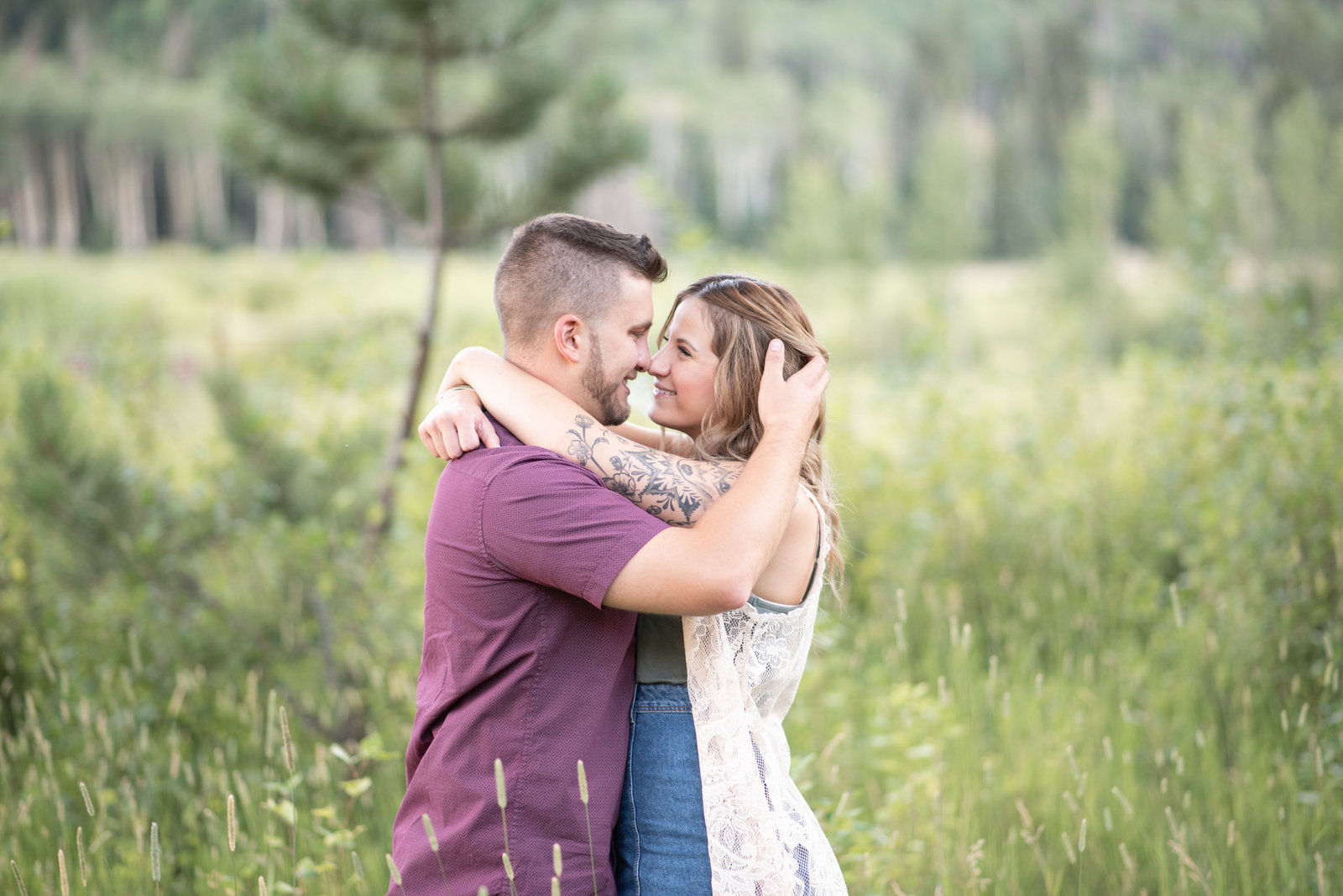 Couple wrapped in eachothers arms during engagement session in RMNP