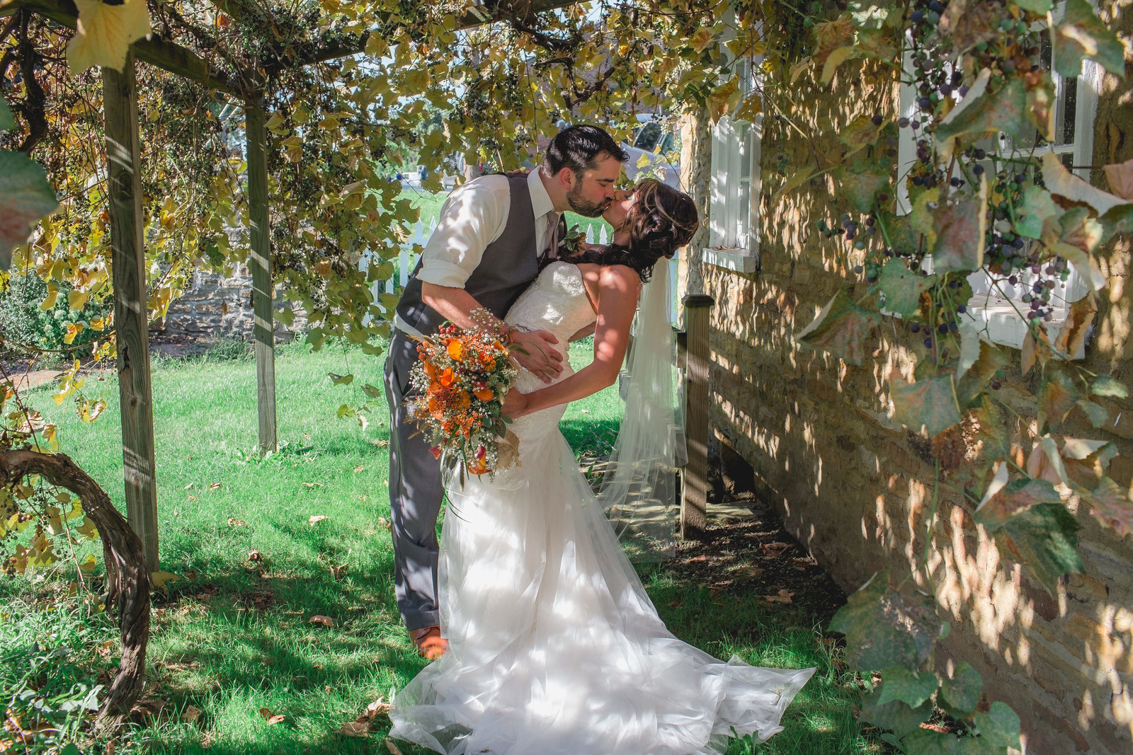 groom dips bride for a kiss under the romantic grapevines near a cabin at west overton