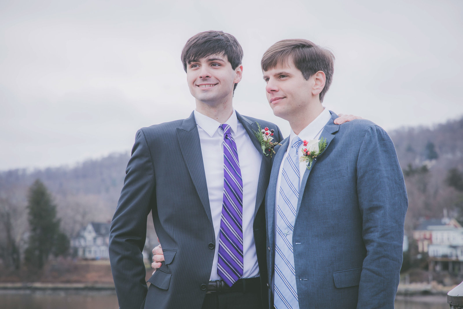 Two grooms gaze off into the distance during their winter elopement.