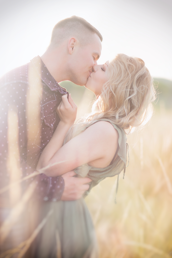 Picture of couple kissing in a field of grass, at Norms Island at River Front Park in Billings, Montana.