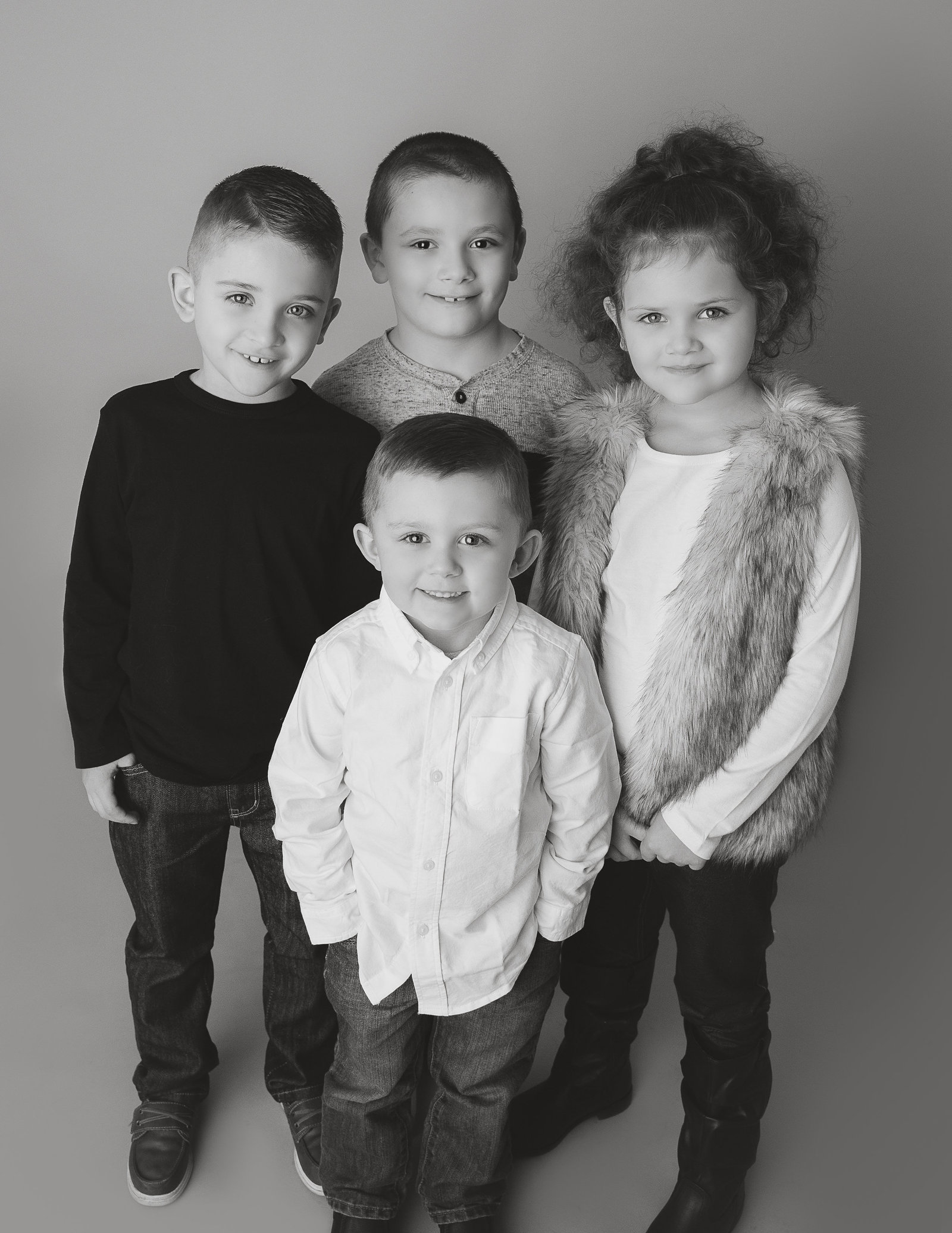 Family session - four cousins standing and smiling - in studio, Rochester NY