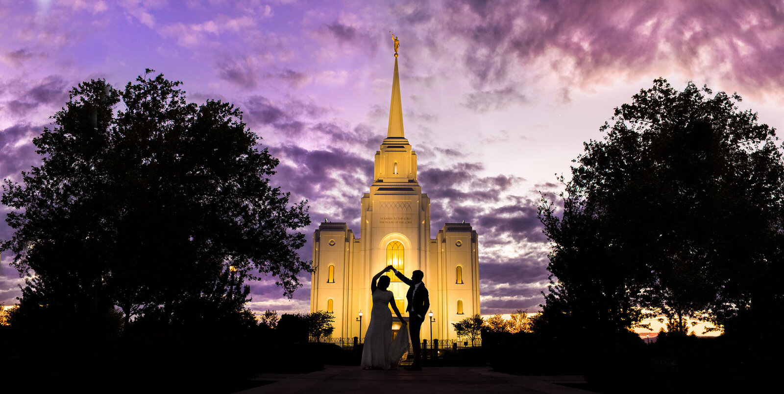 Bride and groom twirl in silhouette in front of LDS temple at sunset