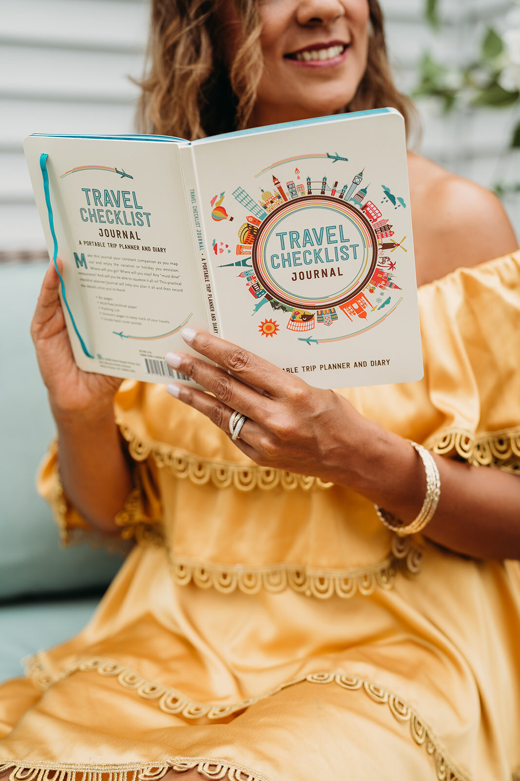 woman holds travel journal in a yellow dress