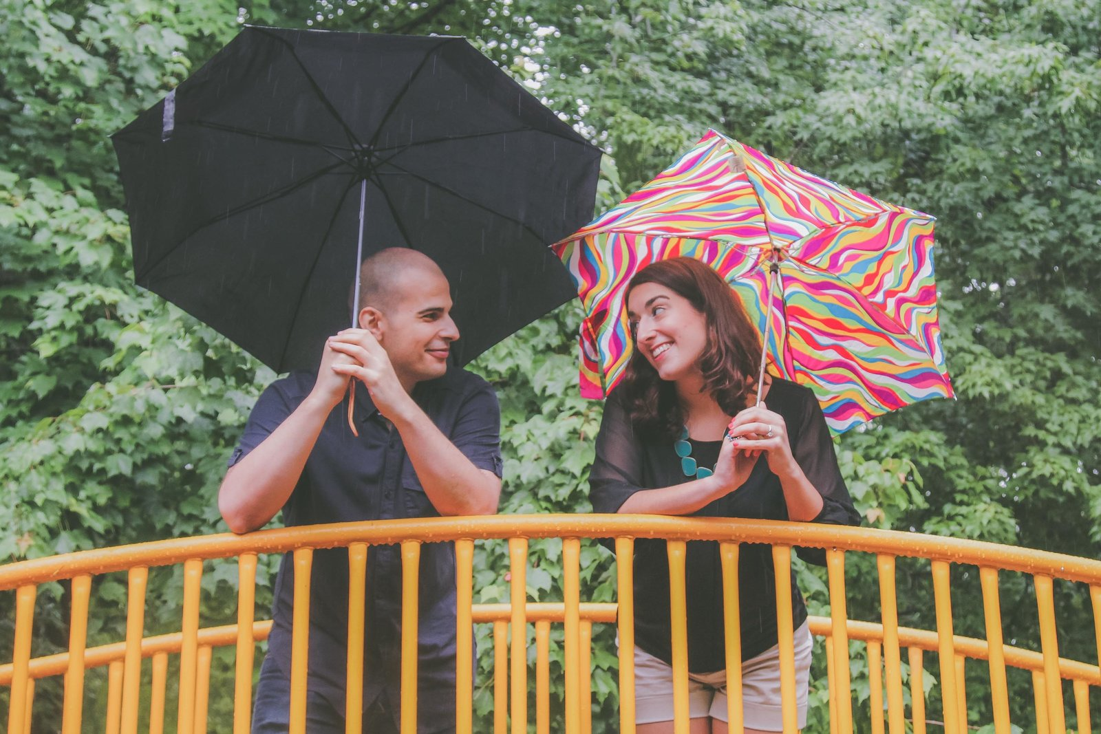 California couple holds umbrellas and look at each other during rain.