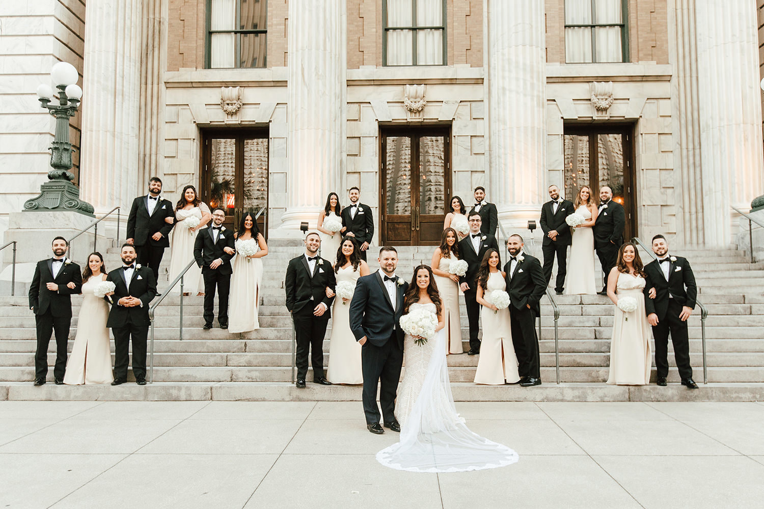 blush and black wedding party posing on steps