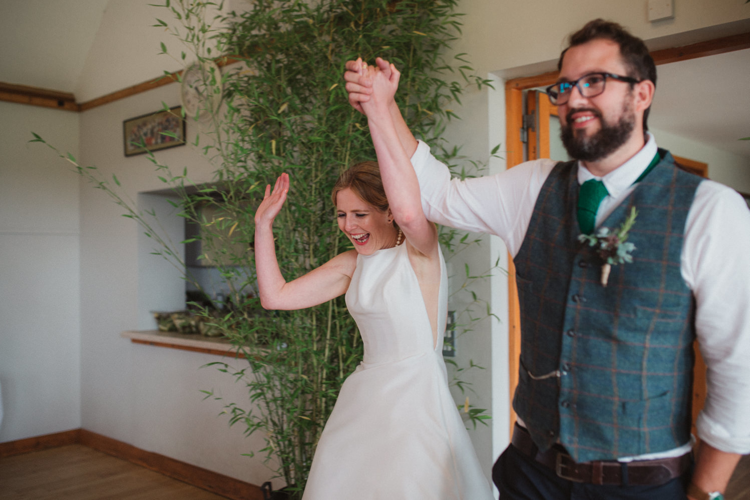 Relaxed newlyweds cheering as they walk in to their Binham Village Hall wedding reception