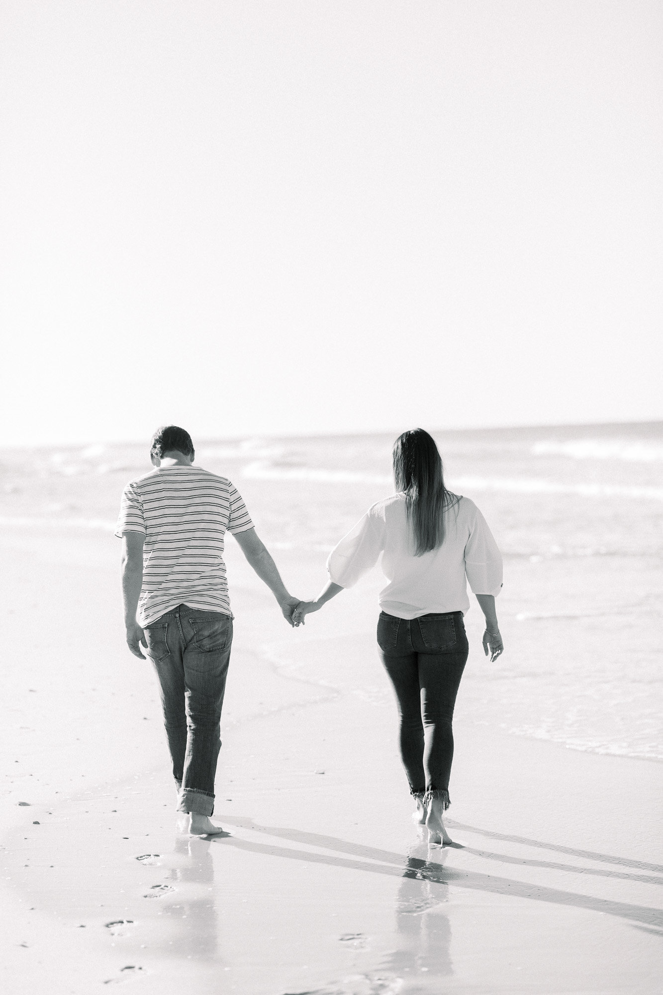 Holding hands on the beach captured by Staci Addison Photography