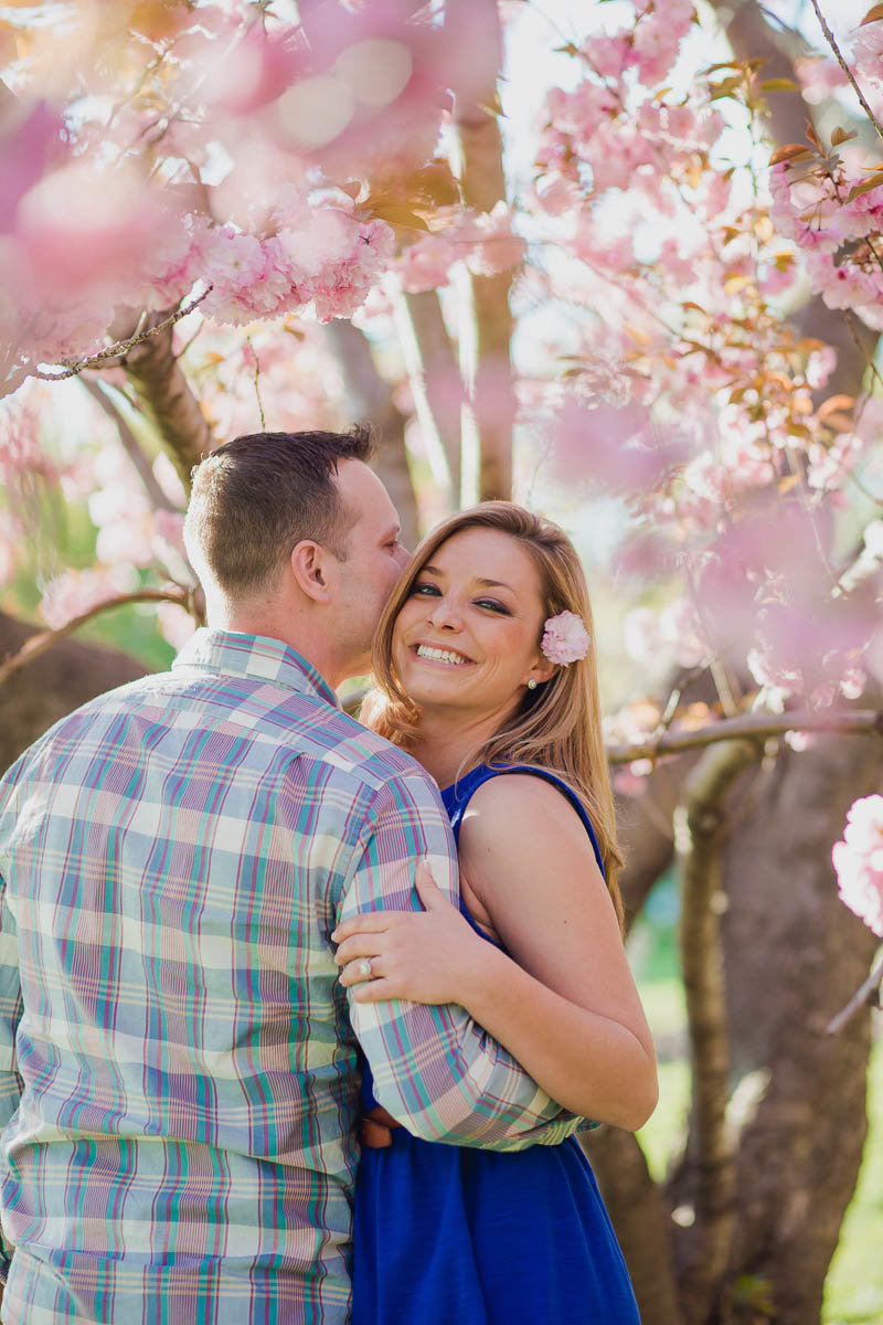 Engaged couple pose under cherry blossom tree in the spring, Boathouse Row, Kelly Drive, Philadelphia, Pennsylvania