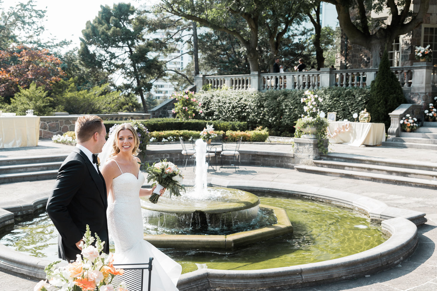 Couple walk around the fountain at this sunny Graydon Hall wedding