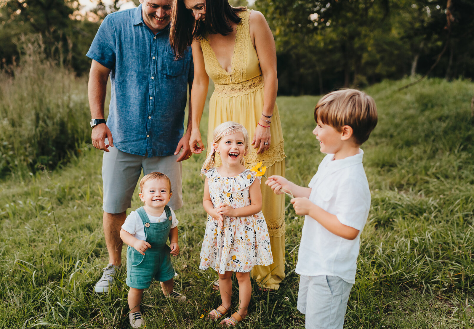family laughing in a field