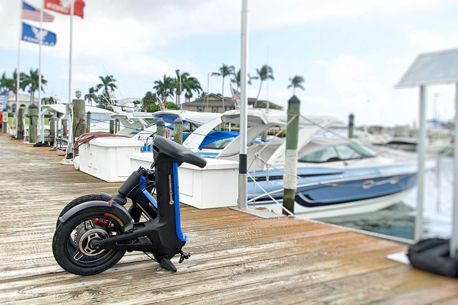 Blue Folded Go-Bike M3 with boat in background
