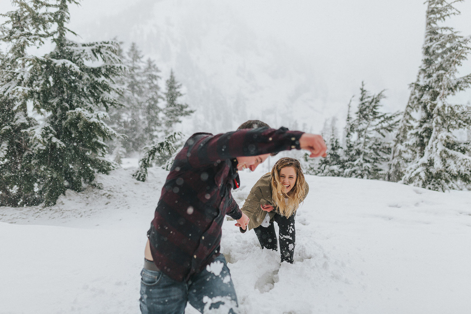 happy engaged couple running through the snow at Mount Baker engagement session