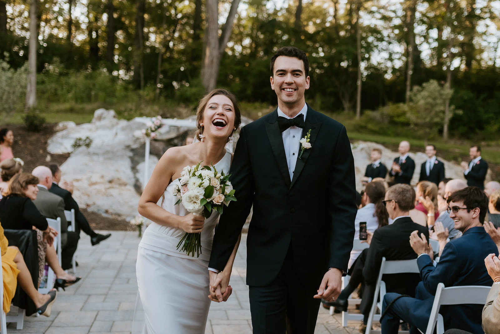 bride and groom in virginia smiling at the end of aisle after marrying