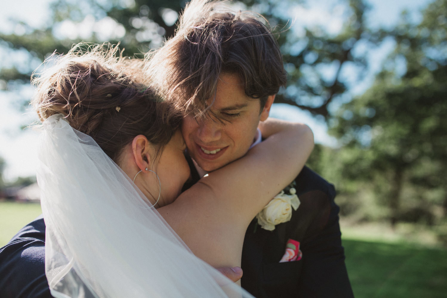 Intimate natural cuddle between newlywed bride and groom at Blackthorpe Barn in Suffolk after their wedding ceremony