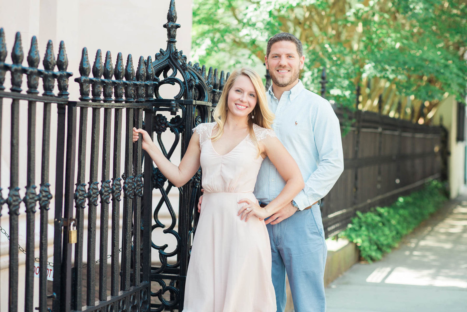 Engaged couple poses by wrought iron gate of Huguenot Church in the French Quarter, Downtown Charleston, South Carolina
