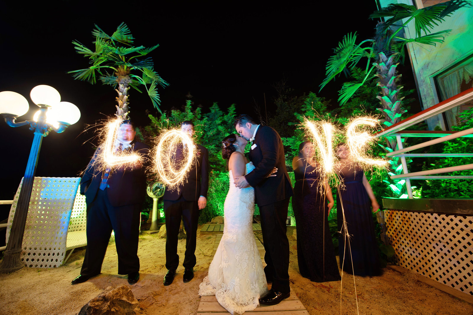 Bride and groom kissing with love in lights at Chateau La Mer