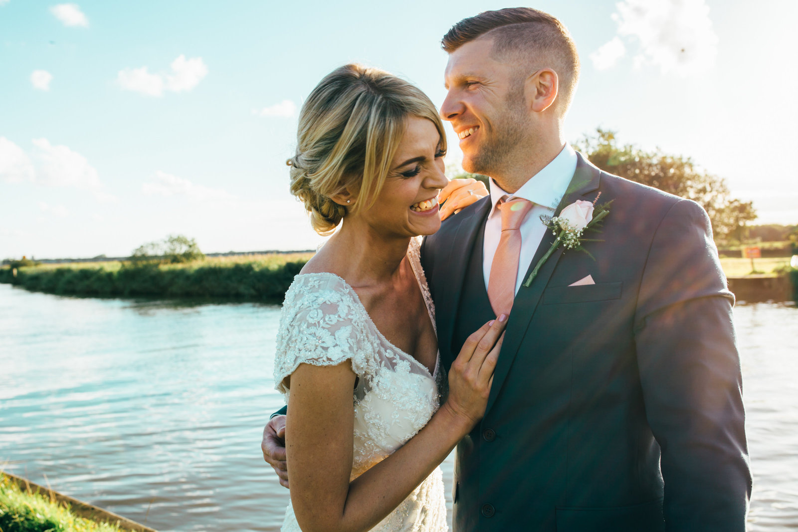 Bride and groom laughing and cuddling by the Norfolk Broads at golden hour