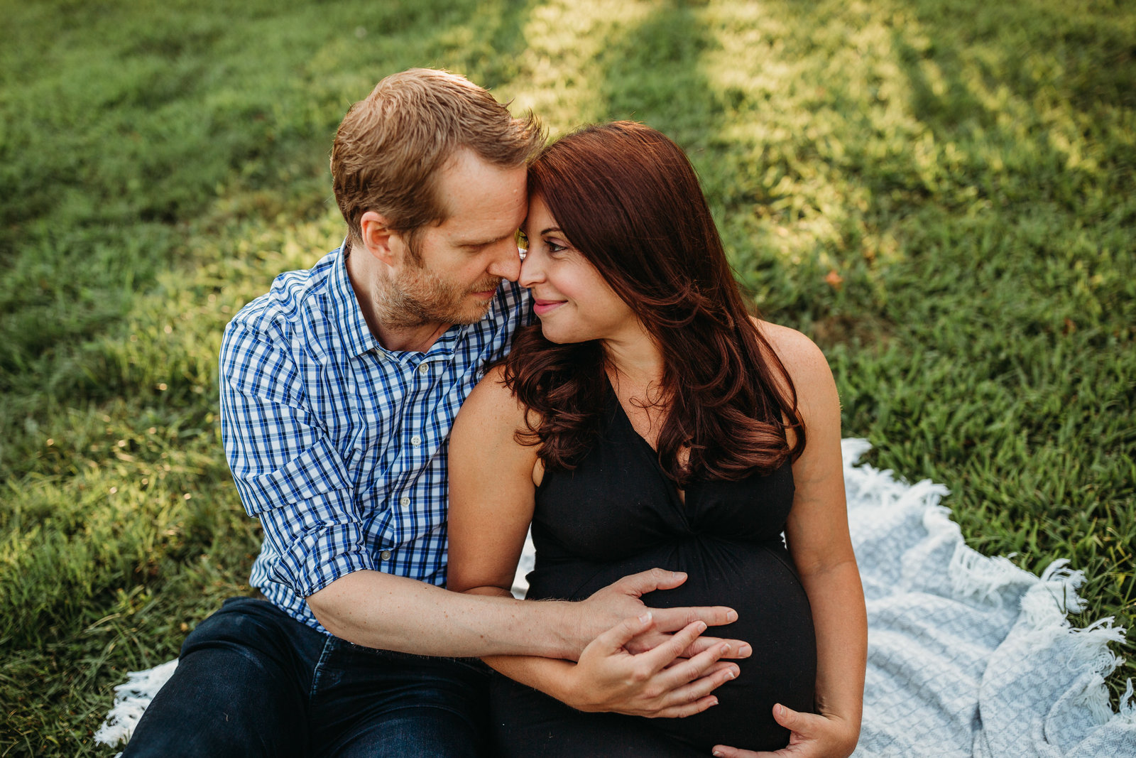 pregnant couple sit on ground in a park in natick ma