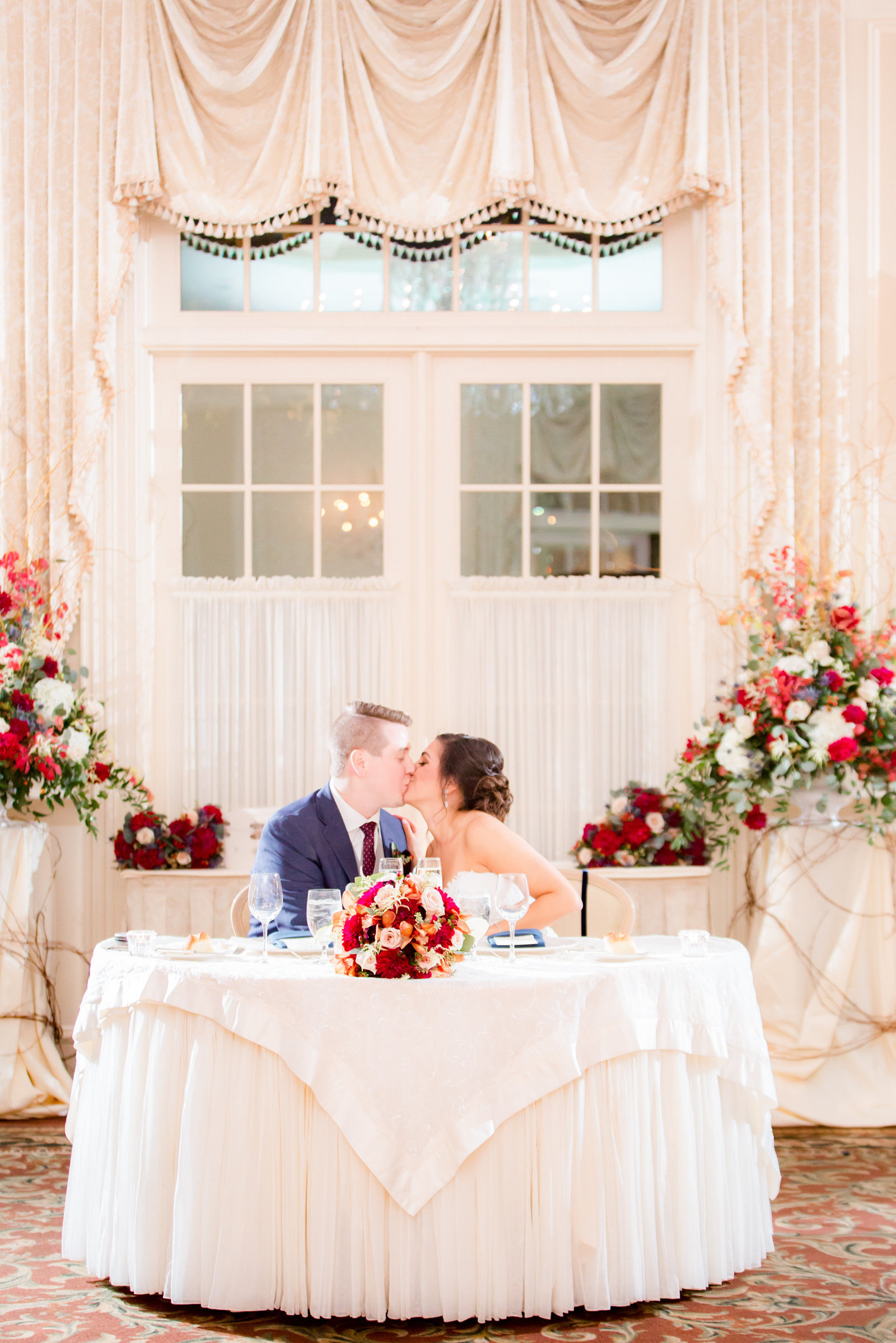 Bride and groom kissing at sweetheart table at Meadow Wood Manor